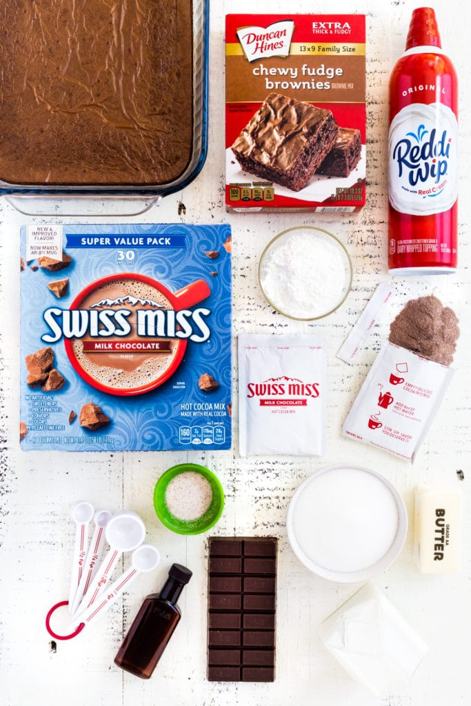 All the ingredients for making homemade chocolate pudding laid out on a white tabletop.
