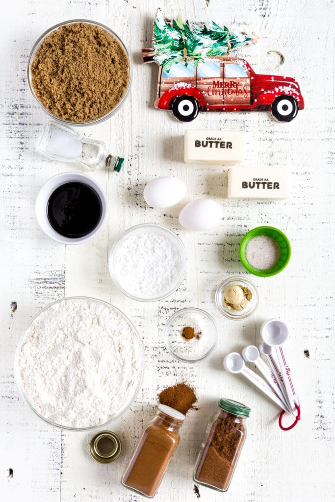 Ingredients for making gingerbread cookies laid out on a white rustic table.