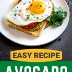 Avocado toast with charred tomatoes and egg on a white plate.