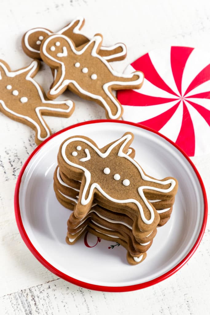 A stack of Gingerbread Man Cookies on a vintage white metal plate with a red rim.
