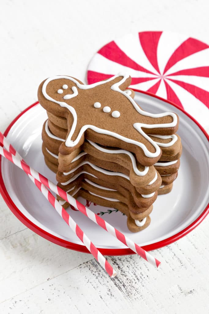 A stack of gingerbread men on a white and red plate next to red-and-white striped drinking straws.