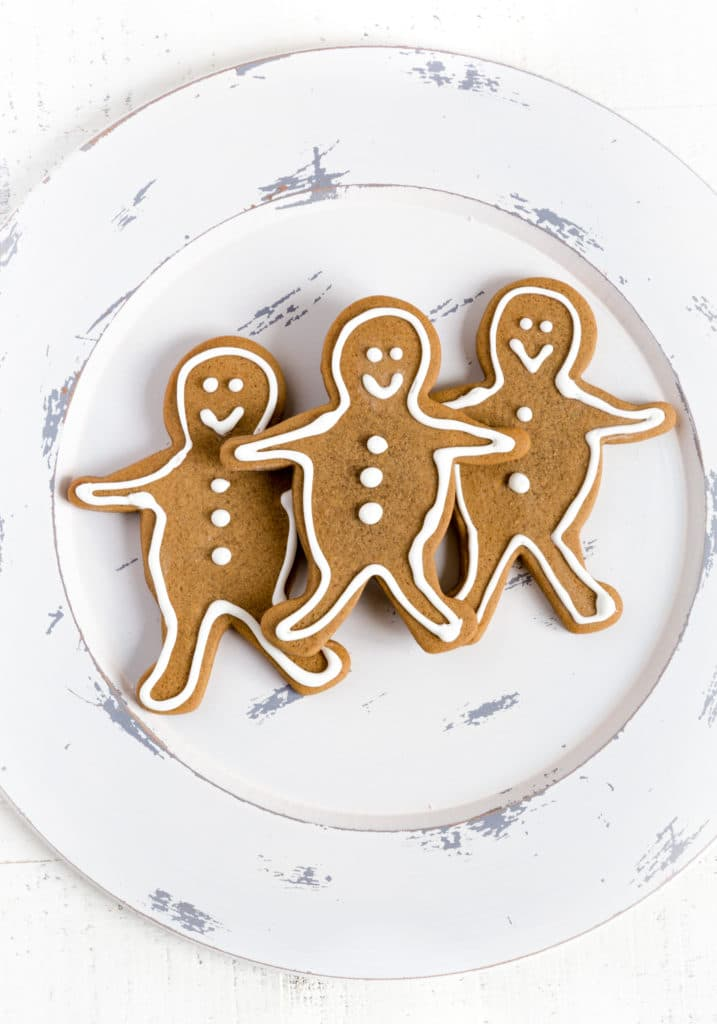 Three gingerbread man cookies on a white plate.