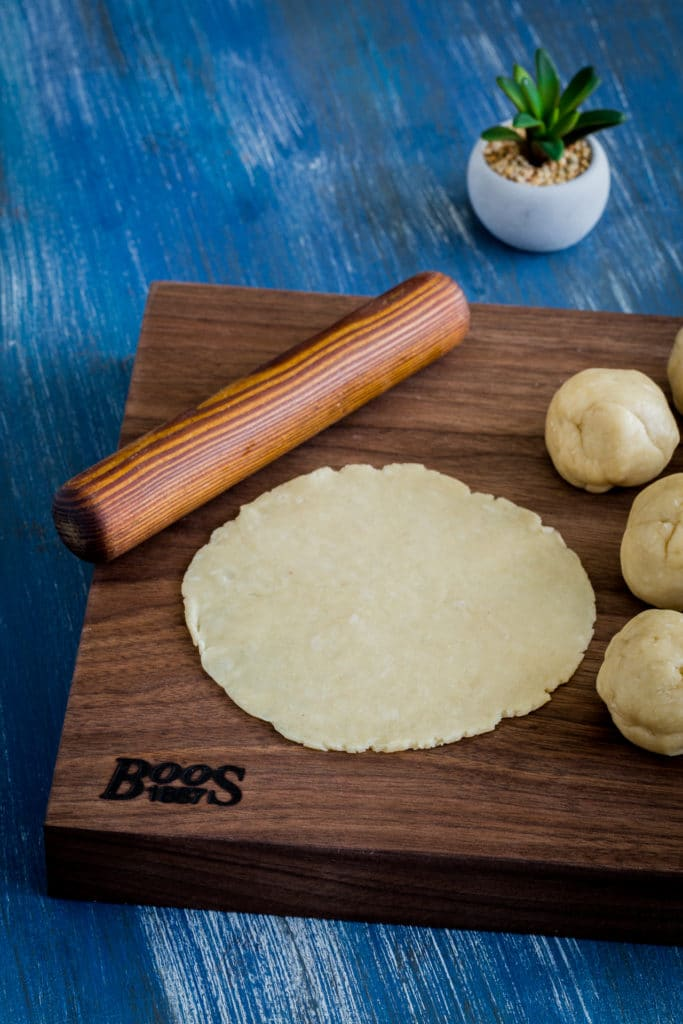 Rolling out empanada dough with a rolling pin and wooden cutting board.