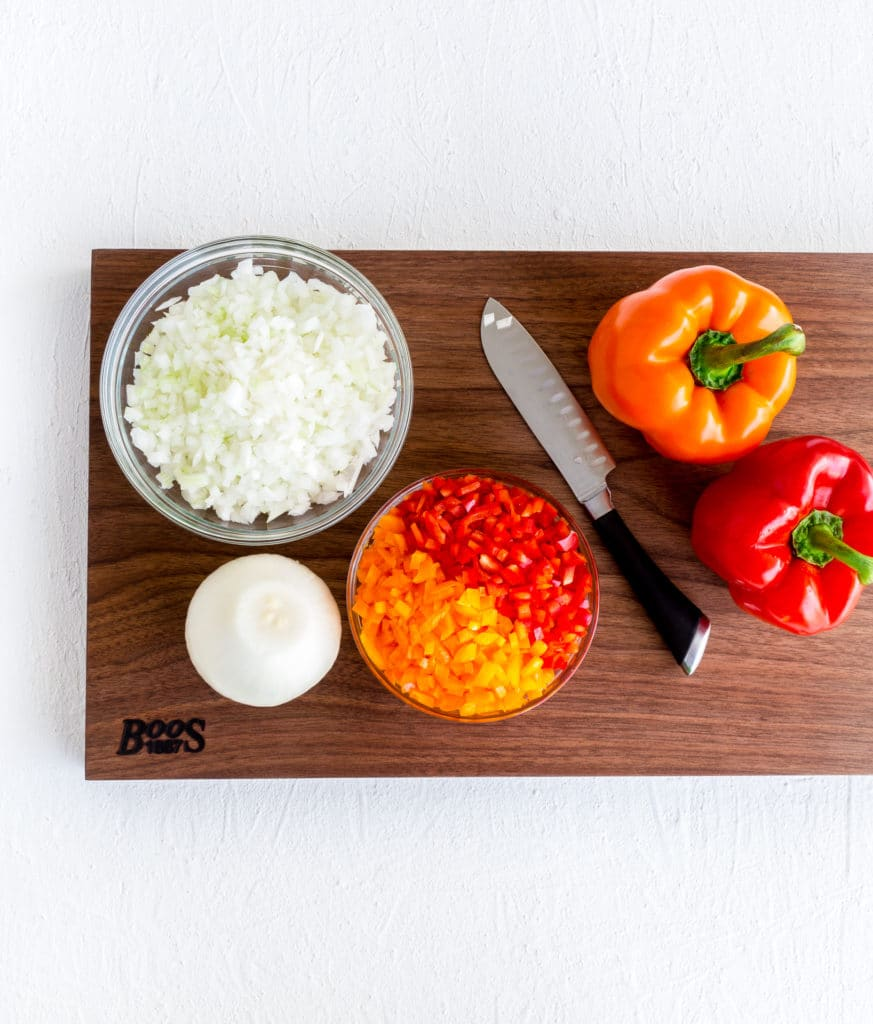 Sliced onions and bell peppers on a Boos cutting board.