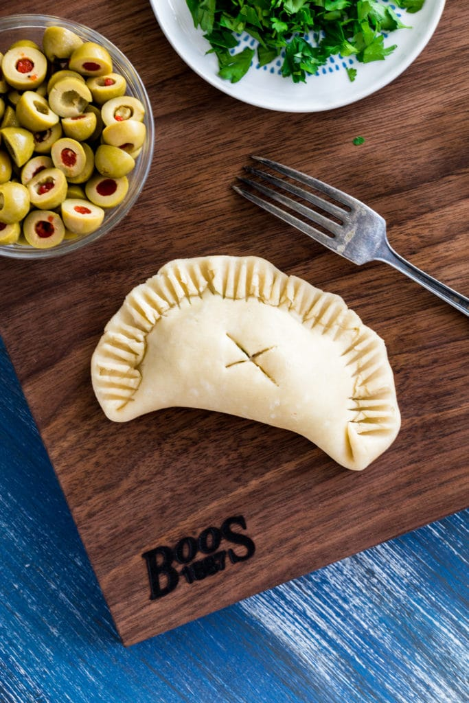 Argentinian empanada on a rustic wooden cutting board.