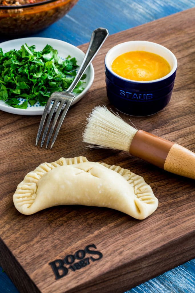A freshly-glazed, unbaked beef empanada next to a pastry brush and bowl of whisked egg.
