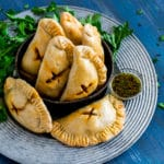 Baked Empanadas on a rustic silver serving tray with chimichurri sauce on the side.