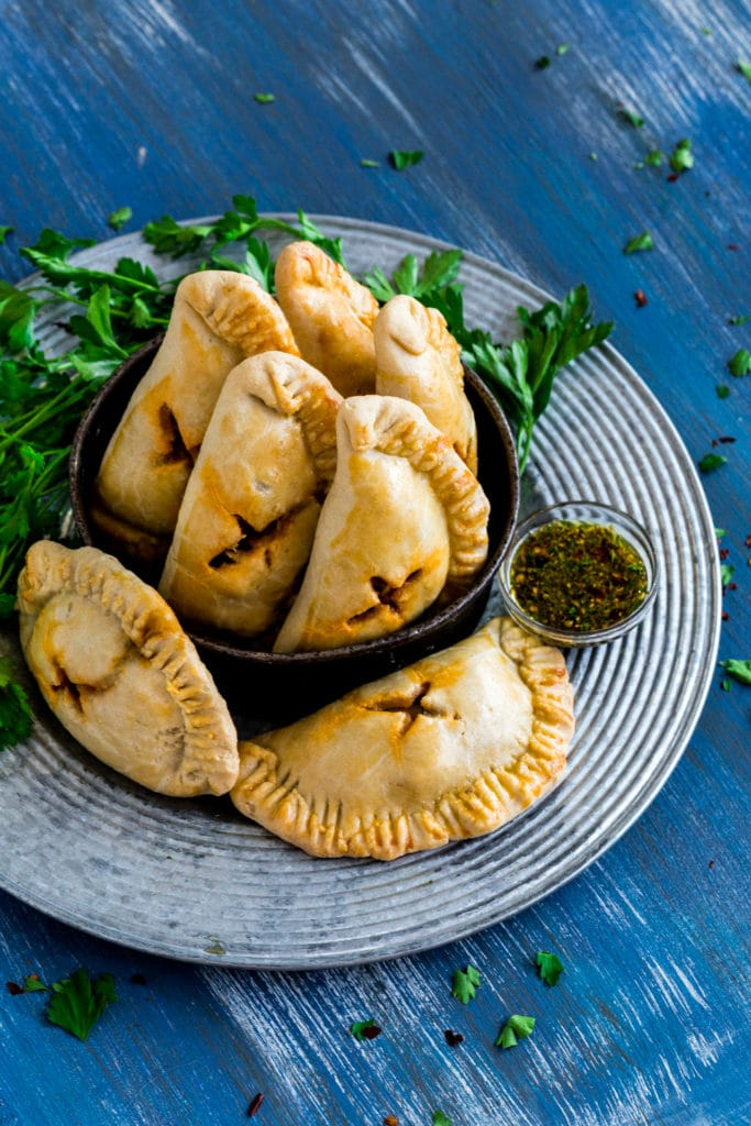 Baked Empanadas on a rustic silver tray with chimichurri sauce on the side.