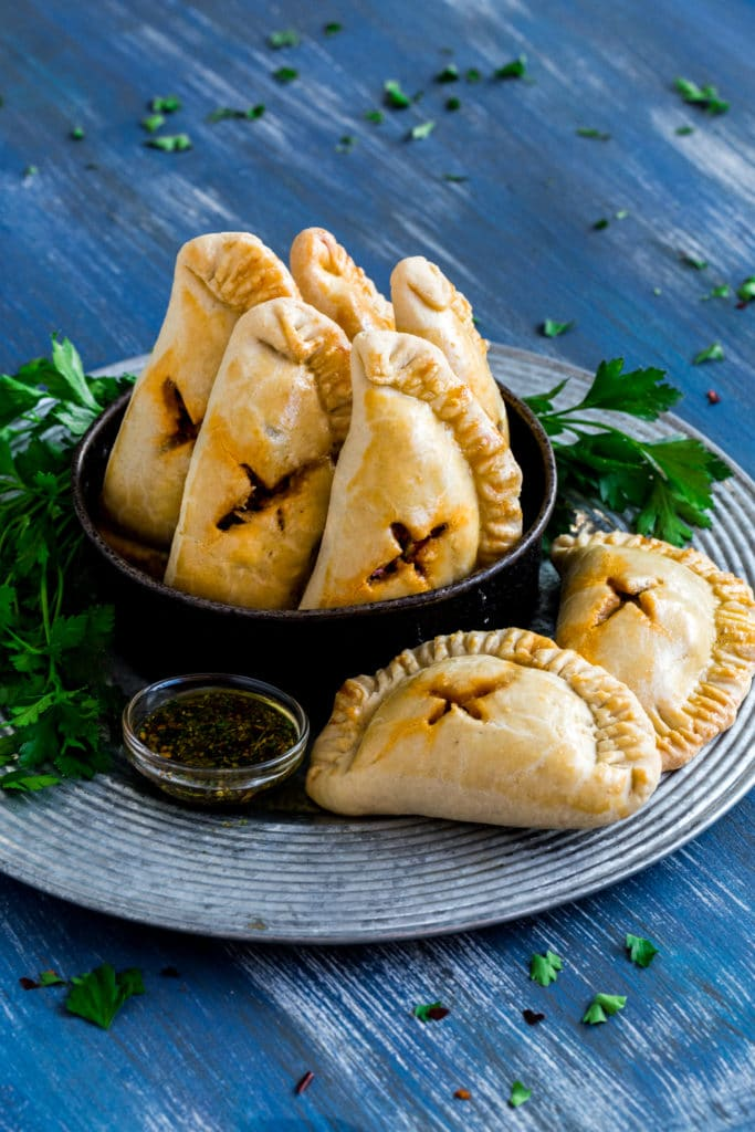 A rustic metal basket filled with Argentinian empanadas.