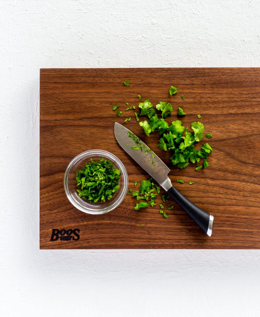 Chopped cilantro with a knife on the surface of a John Boos cutting board.
