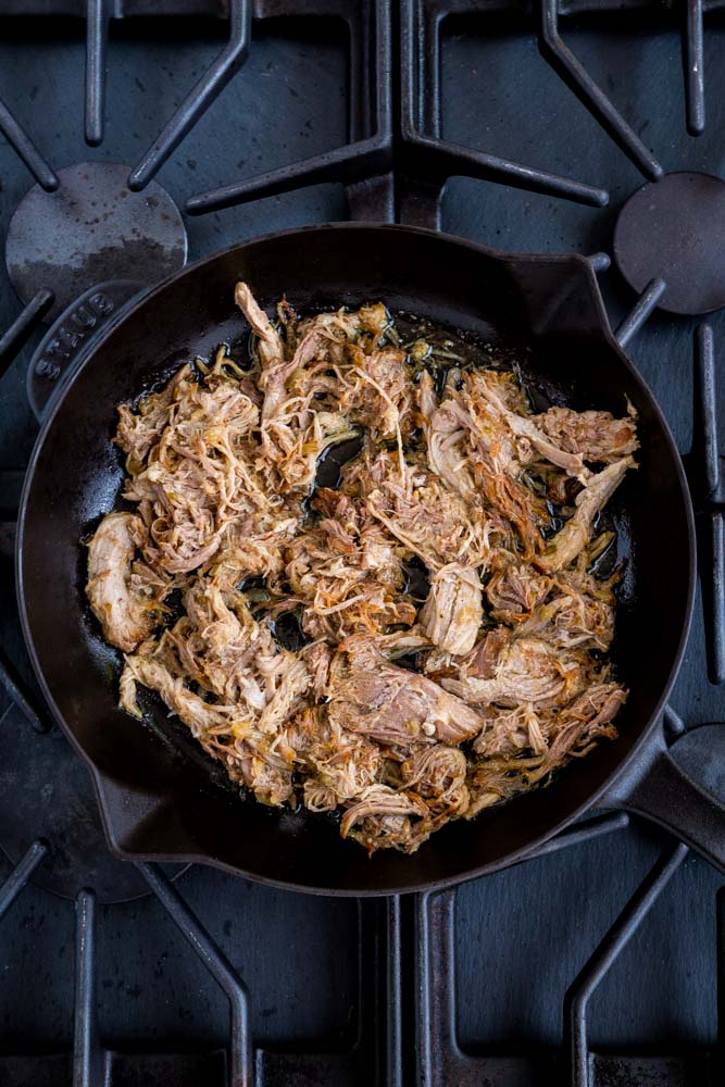 Pork carnitas being fried until golden and crisp in a Staub cast-iron pan.