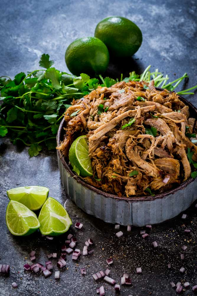 Instant Pot Pork Carnitas served in a rustic metal bowl with limes and cilantro.