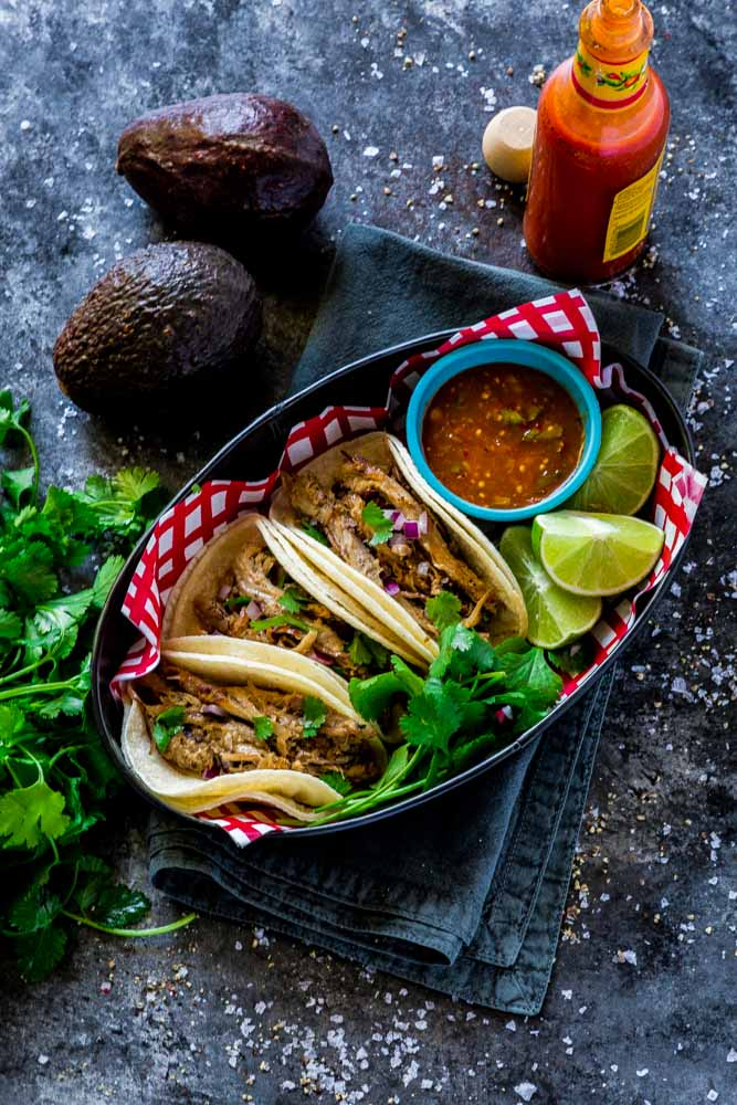 Carnitas tacos served with fresh salsa, cilantro and slices of lime.