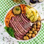 Corned Beef served with cabbage, carrots and potatoes on a white platter.