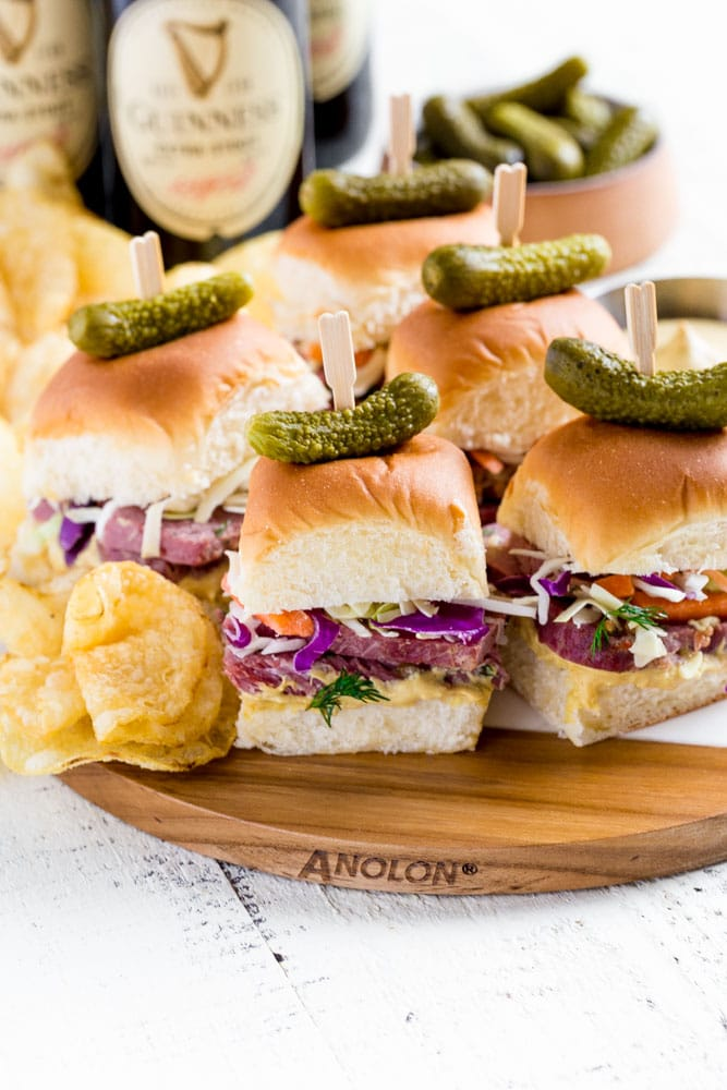 Guinness corned beef sliders on Hawaiian rolls with a pickle on top of each slider sandwich.