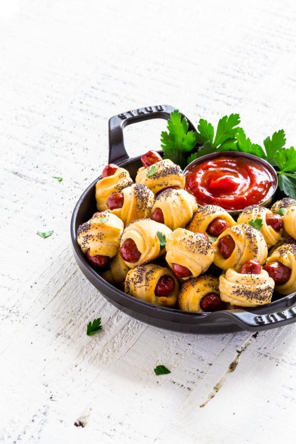 Mini Pigs in a Blanket in a round black Staub dish with ketchup.