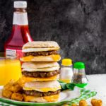 A stack of three sausage egg mcmuffin breakfast sandwiches on a plate.