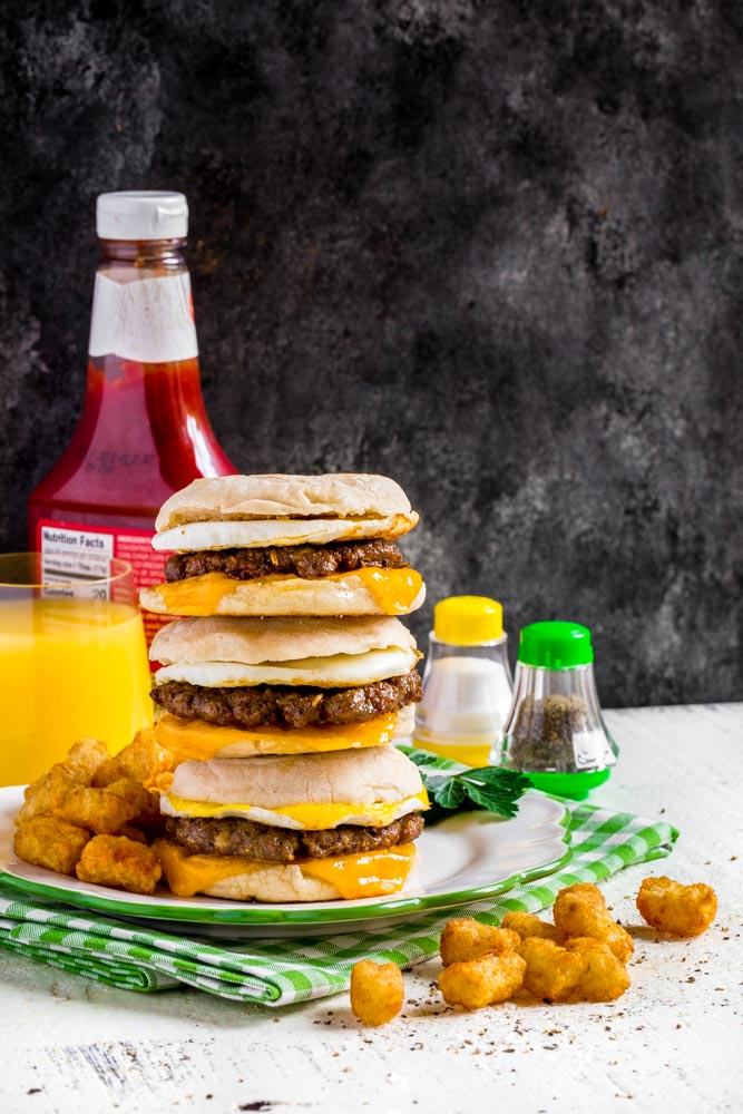 A stack of three homemade Sausage Egg McMuffin breakfast sandwiches on a plate.
