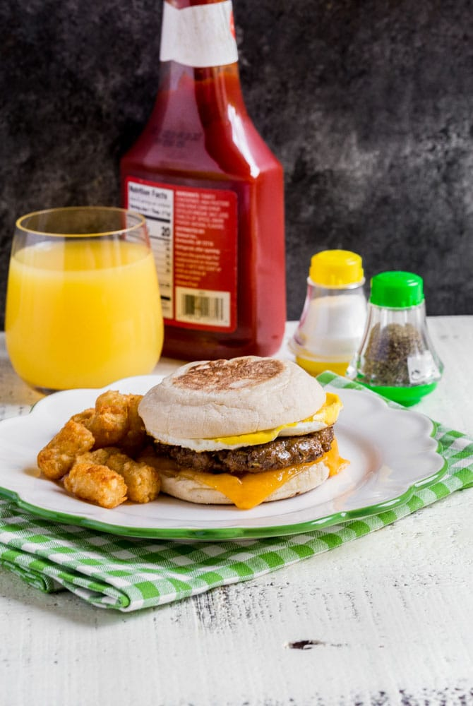 Best breakfast sandwich served on a plate with potatoes and OJ.