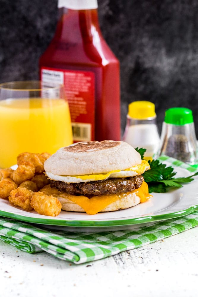 Copycat Sausage and Egg McMuffin with tater tots and orange juice.