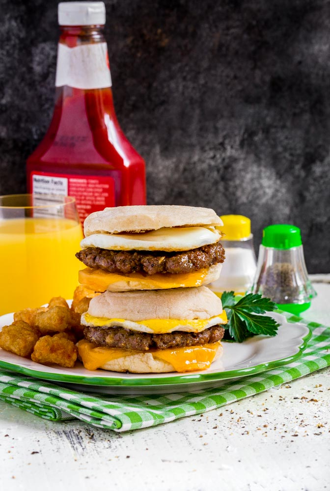 Two homemade Sausage Egg McMuffin sandwiches on a plate with breakfast potatoes.