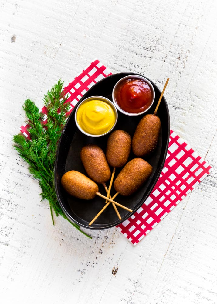 State fair corn dogs served with mustard and ketchup in a metal food tray.