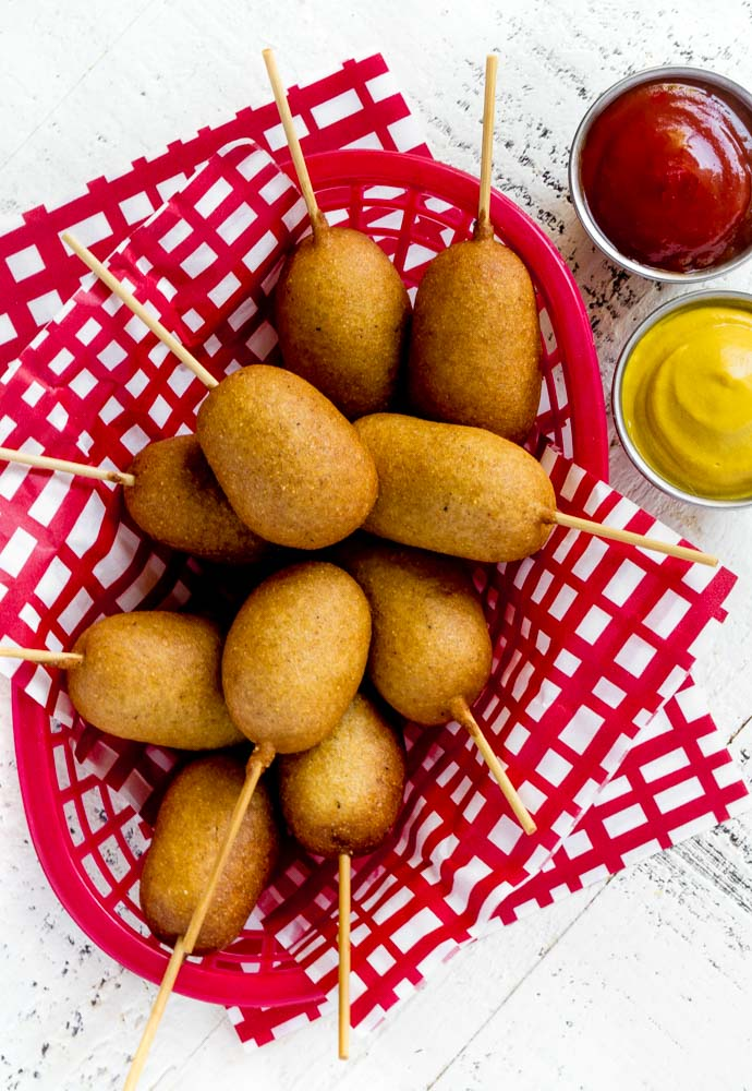 Freshly-made corn dogs in a red checkered serving basket.