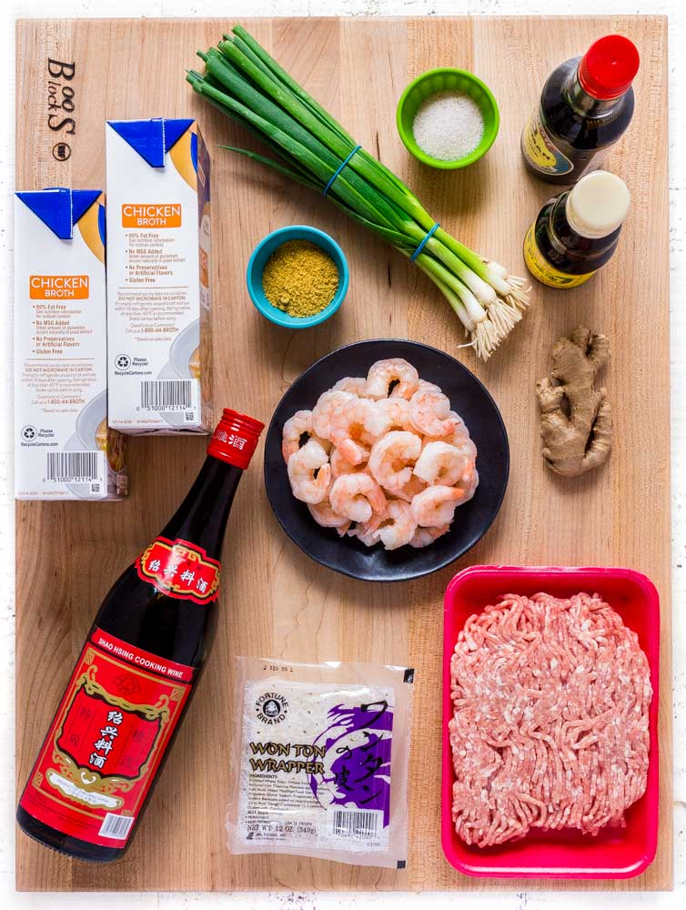 All the ingredients to make wonton soup laid out on a maple Boos block.