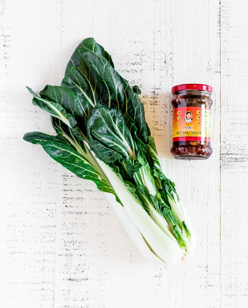 A stalk of Bok choy and a container of Chinese chili oil on a white tabletop.