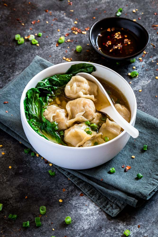Wonton soup served with tender bok choy and hot chili oil on the side.