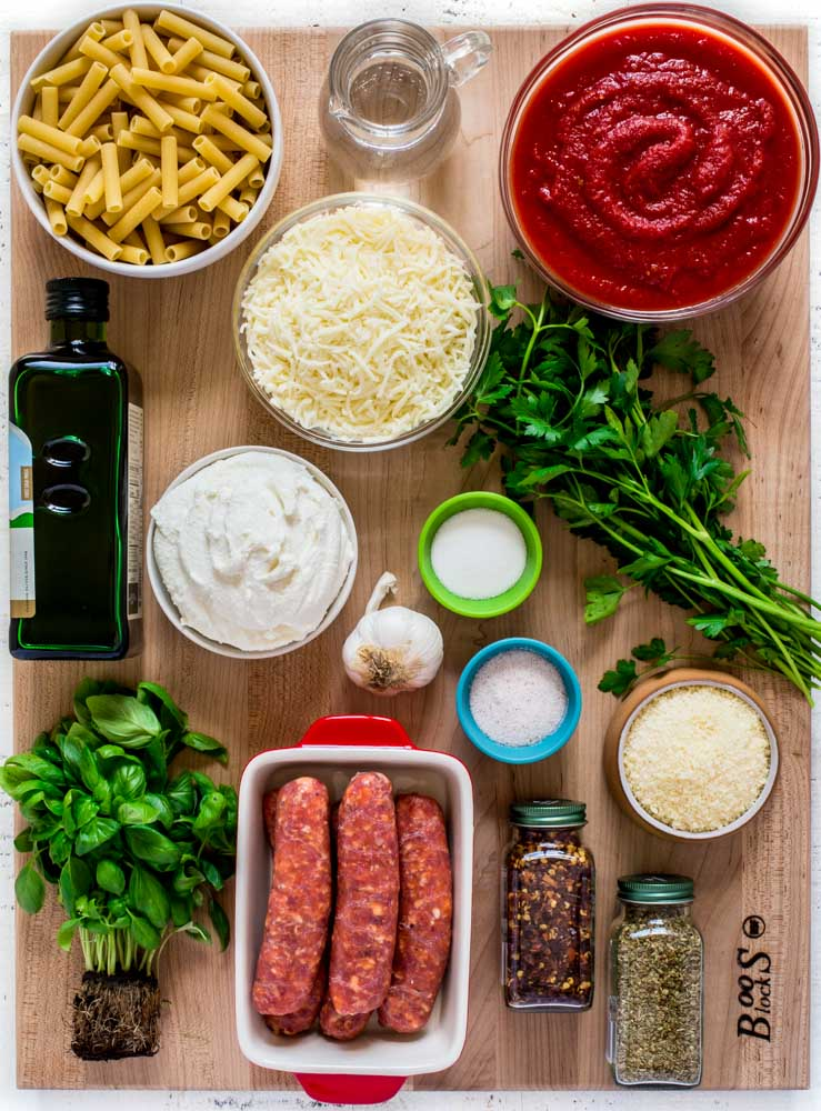 Ingredients for the best baked ziti recipe laid out on a wooden John Boos Board.