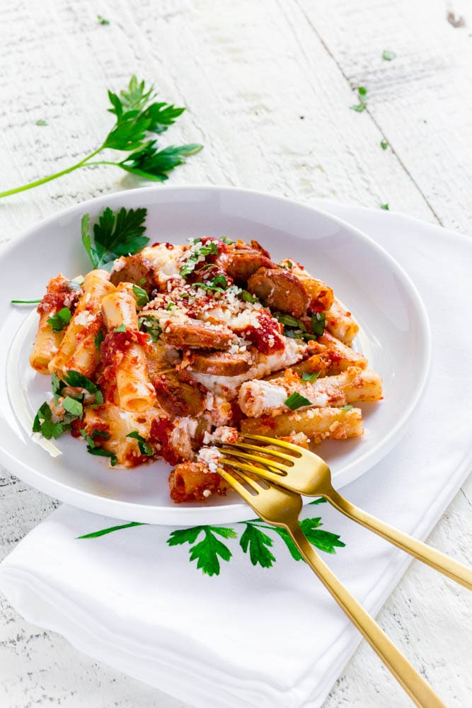 Single serving of baked ziti with ricotta and Italian sausage on a white dinner plate.