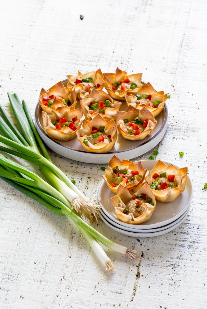 Baked crab rangoon wonton cups on a serving platter and on a white appetizer plate.