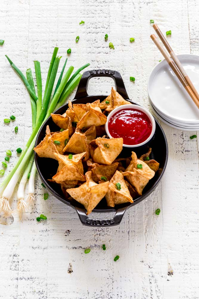 Cream cheese wontons served in a round Staub cast-iron dish.