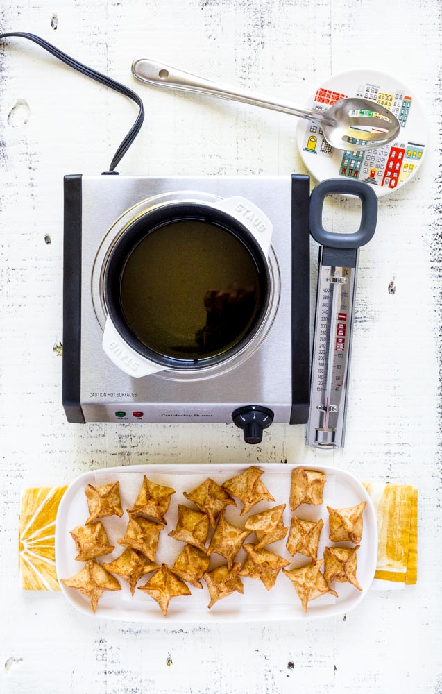 Wontons being fried in a small white Staub cocotte on a tabletop burner.