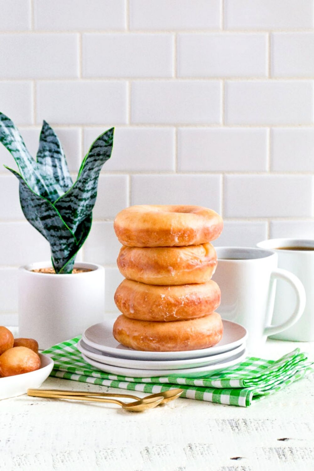 A stack of 4 glazed donuts next to 2 cups of coffee.