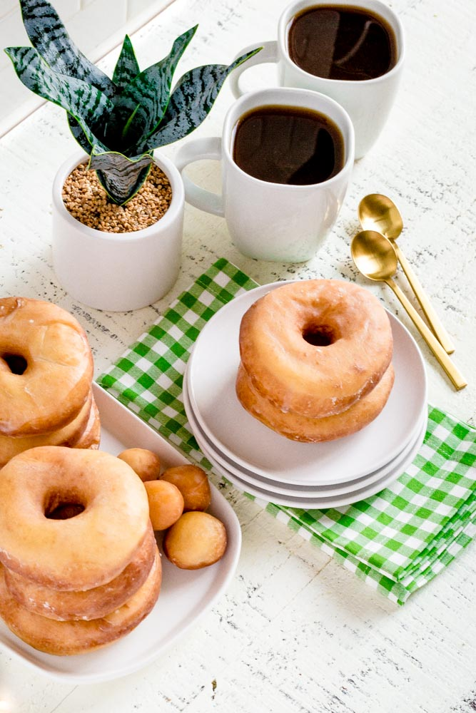 A platter of glazed donuts with serving plates, cups of coffee and gold spoons.