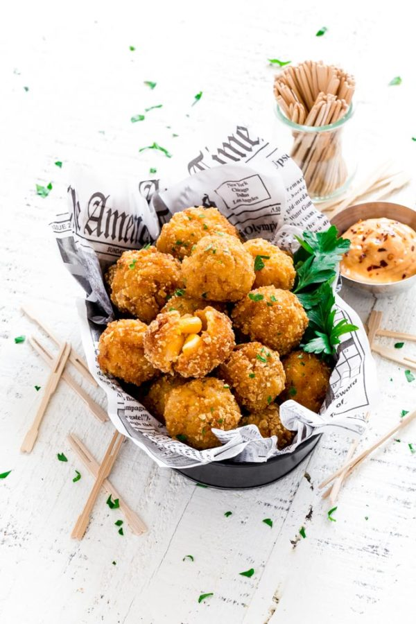 Mac and Cheese Bites sprinkled with parsley and served with bang bang sauce on the side.