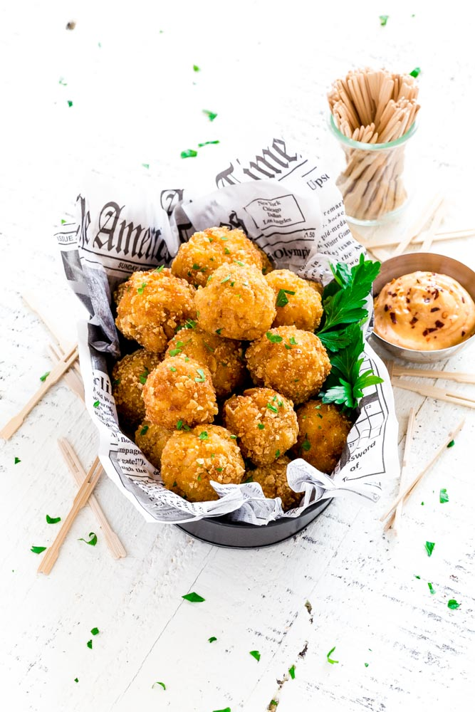 Mac and Cheese Balls served in a restaurant-style metal dish with a newspaper liner.