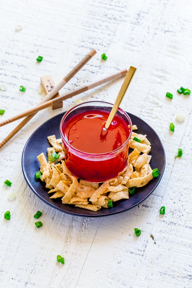 Sweet and Sour Sauce in a small clear-glass bowl with a tiny gold spoon.