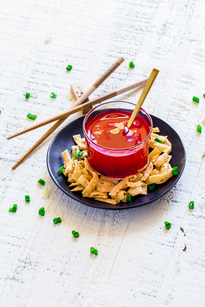Chinese sweet and sour sauce served in a clear glass bowl alongside crispy wonton strips.