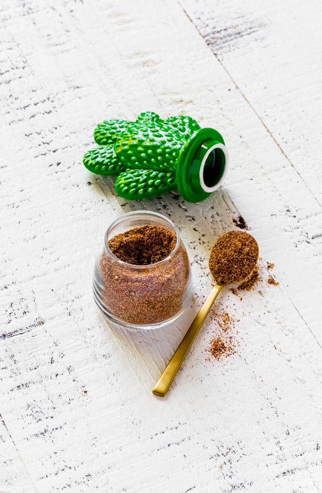 DIY Taco Seasoning in a glass spice jar with green cactus top and small gold spoon.