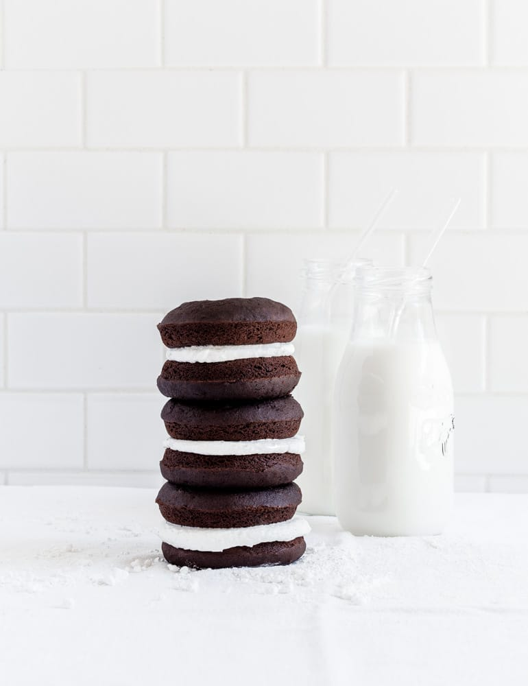 A stack of three whoopie pies with 2 glass bottles of milk against a white background.