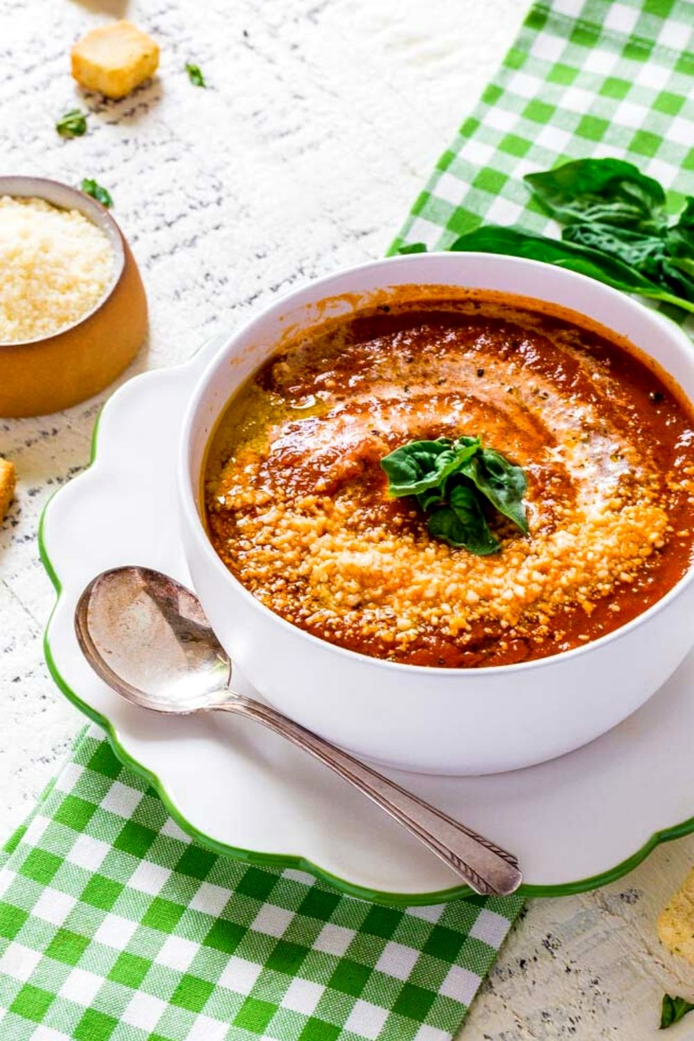 Best tomato basil soup served with a torn-basil garnish and grated parmesan.