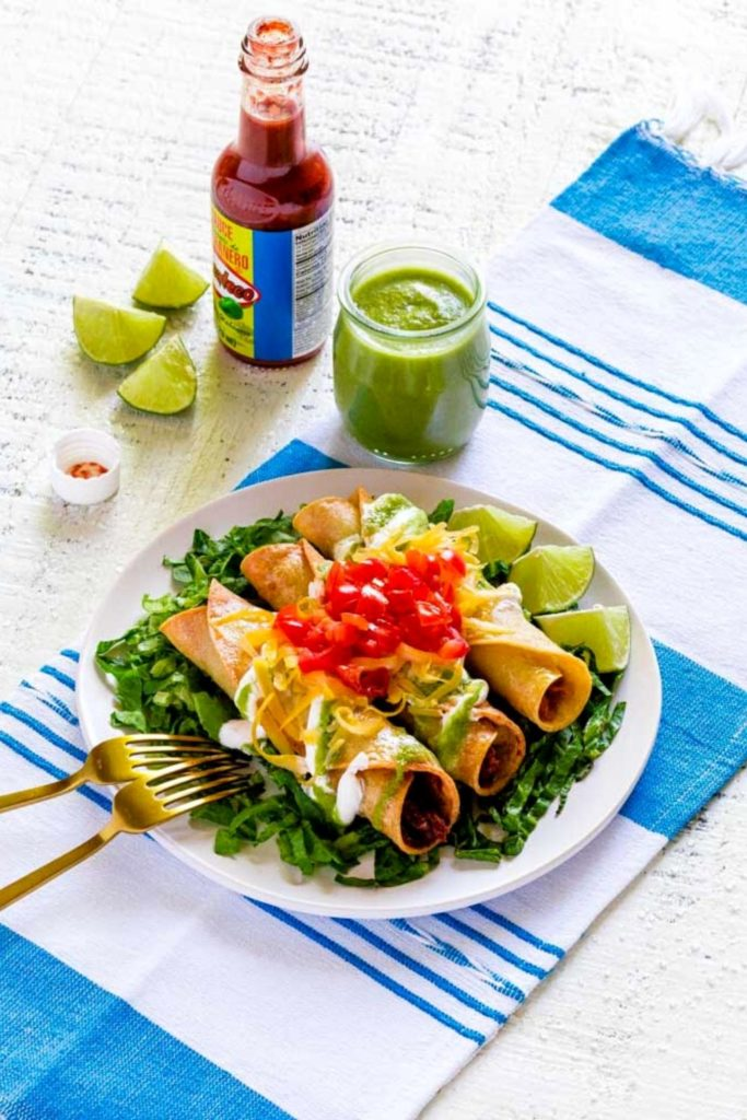 A plate of chicken taquitos with colorful garnishes on a blue-white Mexican table runner.