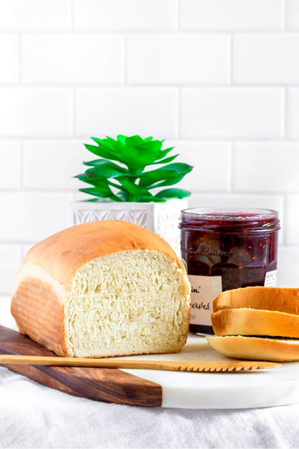 Fresh loaf of homemade white bread on a marble-and-teak board next to a jar of preserves.