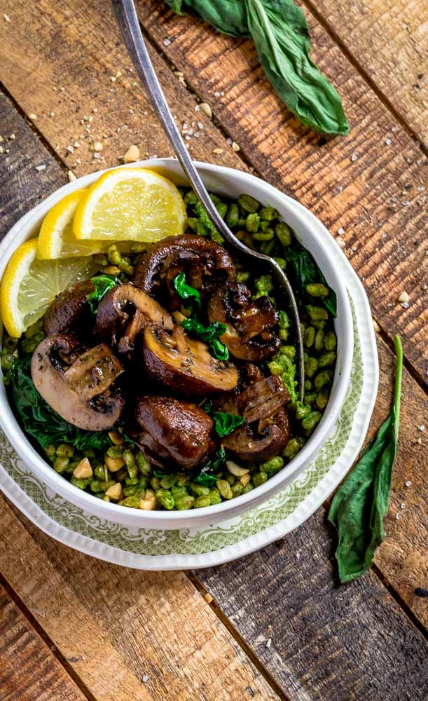 Farrotto served in a bowl, garnished with grilled mushrooms, wilted spinach, sliced lemon and crushed peanuts.