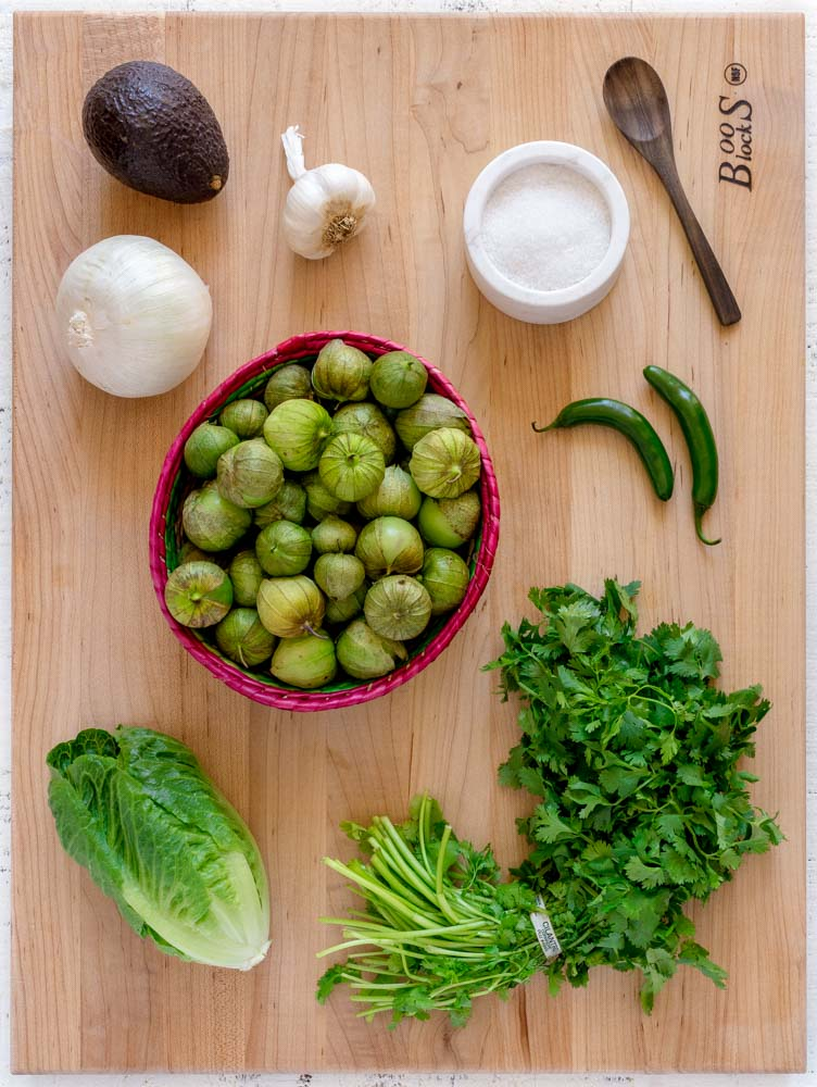 Ingredients for Salsa Verde laid out on a maple board.