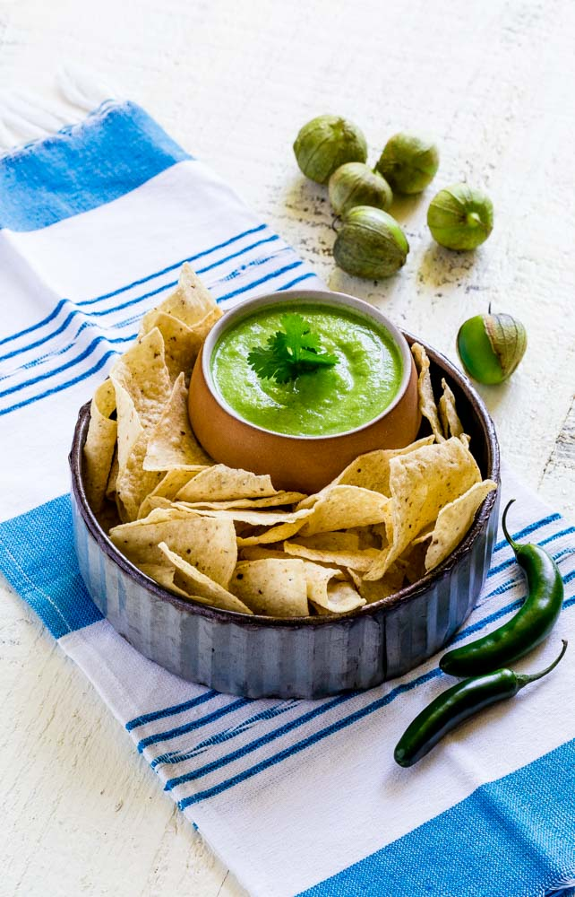 Chips and salsa: Tomatilla Avocado Salsa in a rustic condiment bowl surrounded by tortilla chips.