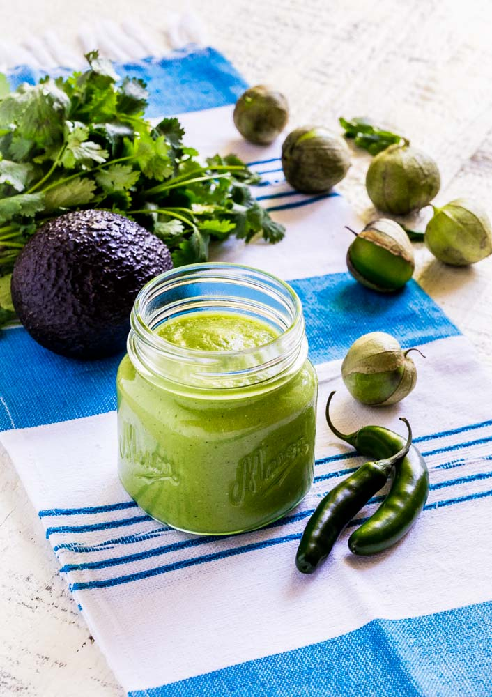 A clear glass jar with green salsa, AKA salsa verde on a rustic white tabletop.